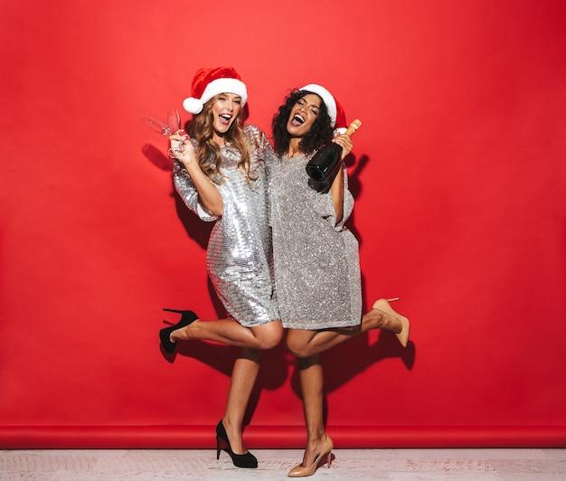 Sur toute la longueur de deux joyeuses jeunes femmes bien habillées célébrant le nouvel an sur l'espace rouge