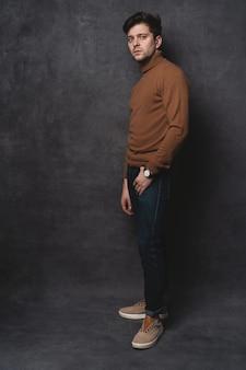 Sur toute la longueur du beau jeune homme à la recherche. portrait de jeune homme avec les mains dans les poches appuyé contre le mur gris