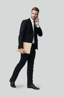 Toute la longueur du beau jeune homme en tenue de soirée parlant au téléphone en se tenant debout sur fond gris