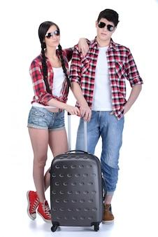 Toute la longueur du jeune couple marchant avec des valises de voyage.
