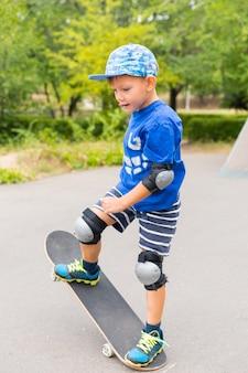Toute la longueur du jeune garçon déterminé portant des coussinets de sécurité et une casquette faisant un tour simple sur une planche à roulettes dans un parc de skate le jour d'été