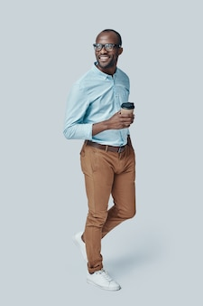 Toute la longueur du jeune homme africain confiant regardant loin et souriant tout en se tenant contre le mur gris