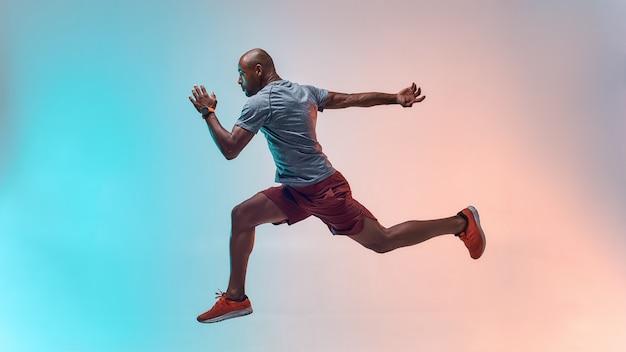 Toute la longueur du jeune homme africain en vêtements de sport sautant sur fond coloré
