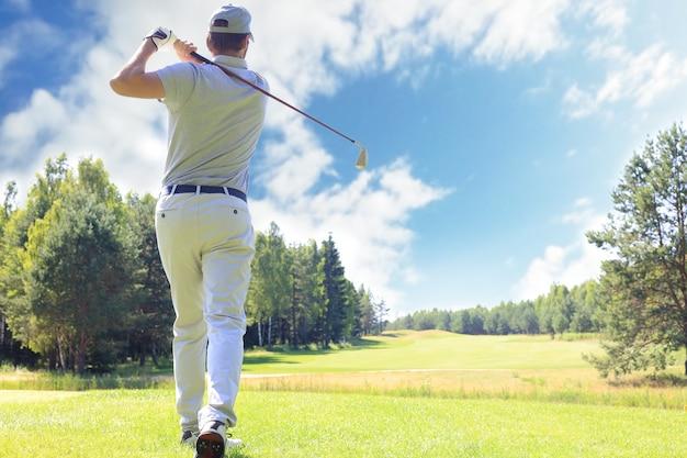 Toute la longueur du joueur de golf jouant au golf par beau temps. golfeur masculin professionnel tirant sur le terrain de golf.