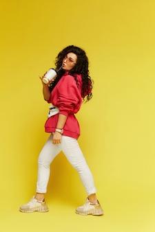 Sur toute la longueur, l'élégant modèle femme en sweat à capuche rose et pantalon blanc tenant une tasse de café en papier et profiter de la boisson, isolée sur le mur jaune