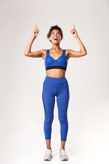 Toute la longueur de la femme afro-américaine excitée et heureuse en tenue de sport pour l'entraînement, à la recherche et