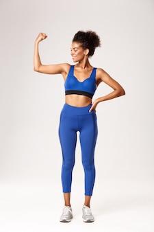 Toute la longueur de la femme afro-américaine souriante satisfaite avec un corps parfait, portant des vêtements de sport, flex