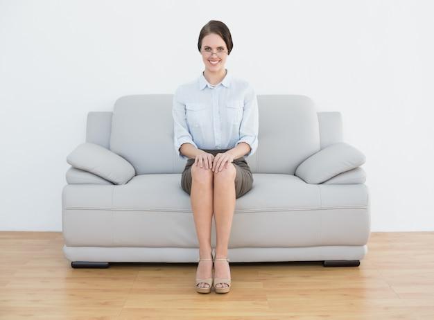 Toute la longueur d'une femme bien habillée souriante assise sur le canapé