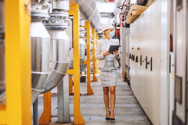 Toute la longueur de la femme blonde en tenue de soirée, avec casque sur la tête, avec masque de protection marchant à travers l'installation de chauffage et utilisant une tablette pour vérifier les machines.