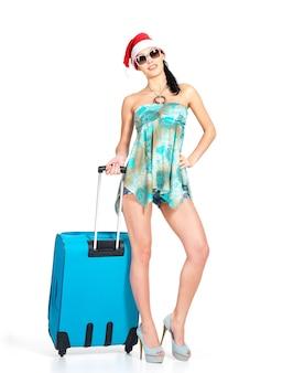 Toute la longueur de la femme en bonnet de noel debout avec valise de voyage