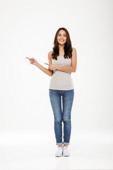 Toute la longueur de femme brune heureuse pointant sur la surface et regardant la caméra sur gris