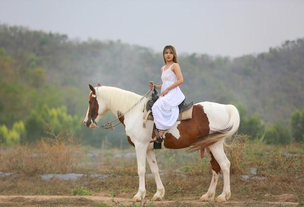Toute la longueur de la femme à cheval sur le terrain par des arbres contre le ciel.