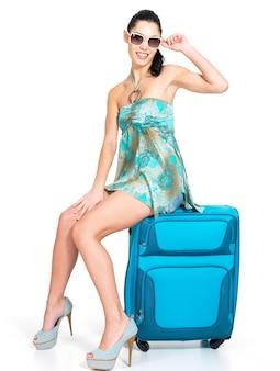 Toute la longueur de la femme décontractée debout avec valise de voyage