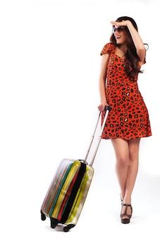 Toute la longueur de la femme occasionnelle debout avec une valise de voyage - isolé sur fond blanc