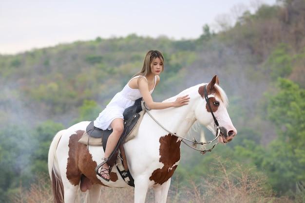 Toute la longueur de la femme en robe à cheval sur le terrain par des arbres contre le ciel