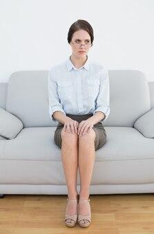 Toute la longueur d'une femme sérieuse bien habillée sur le canapé