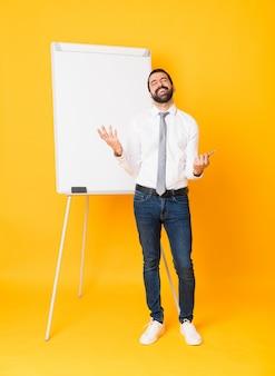 Toute la longueur de l'homme d'affaires donnant une présentation sur un tableau blanc sur un mur jaune isolé souriant beaucoup