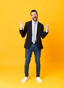 Toute la longueur de l'homme d'affaires sur un mur jaune isolé, geste de roche