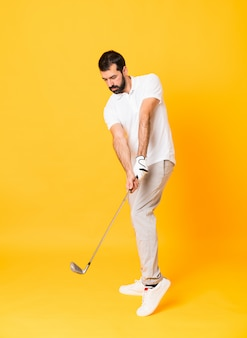 Toute la longueur d'un homme jouant au golf sur un mur jaune isolé