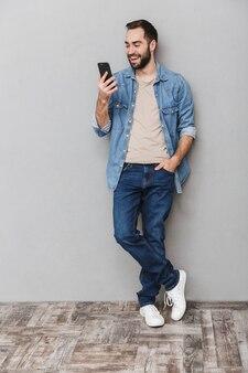 Sur toute la longueur d'un homme joyeux excité portant une chemise sur un mur gris, à l'aide d'un téléphone mobile