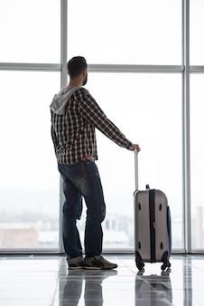 Toute la longueur d'un homme avec une valise en attendant.