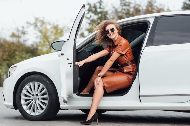 Toute la longueur d'une jeune femme d'affaires confiante qui sort de son véhicule