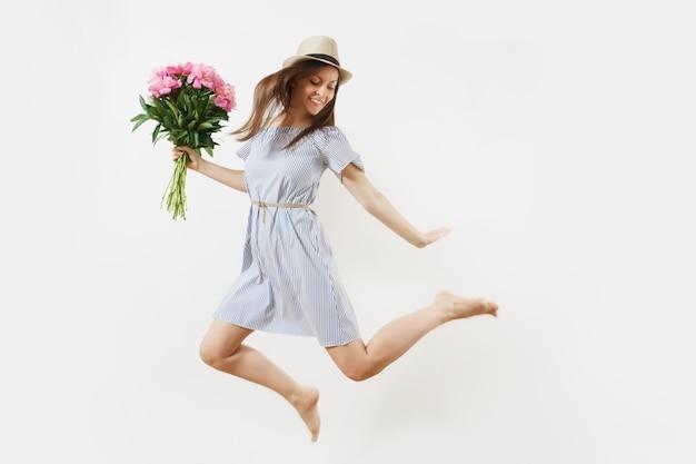 Toute la longueur d'une jeune femme heureuse et amusante en robe bleue, chapeau tenant un bouquet de fleurs de pivoines roses, sautant isolé sur fond blanc. saint-valentin, concept de vacances de la journée internationale de la femme.