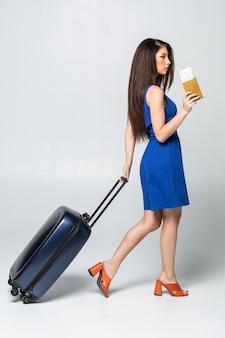 Toute la longueur de la jeune femme en marche décontractée avec le sac de voyage, isolé