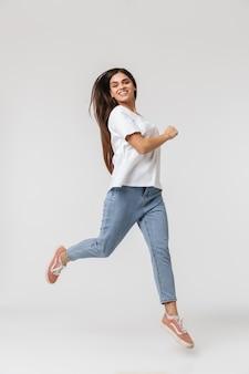 Sur toute la longueur d'une jeune femme souriante habillée décontractée sautant isolé sur blanc