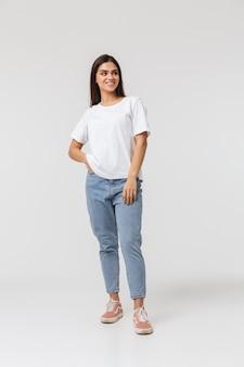 Sur toute la longueur d'une jeune femme souriante habillée occasionnellement debout isolé sur blanc