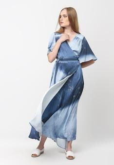 Toute la longueur d'une jeune fille élégante dans une robe d'été bleu clair