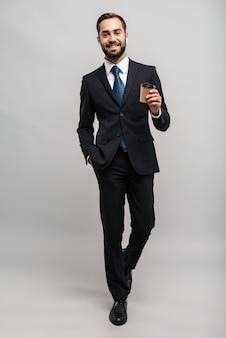 Toute la longueur d'un jeune homme d'affaires souriant et séduisant portant un costume isolé sur un mur gris, portant des écouteurs tout en buvant du café à emporter