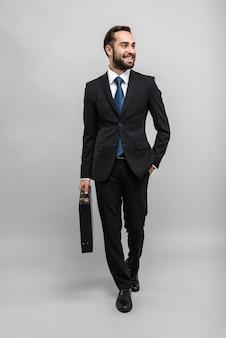Toute la longueur d'un jeune homme d'affaires souriant et séduisant portant un costume isolé sur un mur gris, portant une mallette, marchant