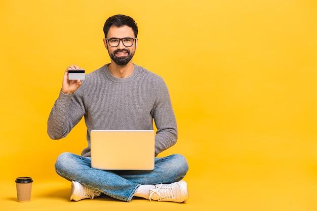 Sur toute la longueur d'un jeune homme joyeux assis avec les jambes croisées isolé sur fond jaune, à l'aide d'un ordinateur portable, montrant la carte de crédit.