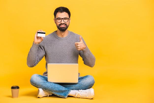 Sur toute la longueur d'un jeune homme joyeux assis avec les jambes croisées isolé sur fond jaune, à l'aide d'un ordinateur portable