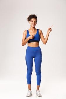 Toute la longueur de la jolie femme afro-américaine souriante aux cheveux peignés, portant des vêtements de sport bleus