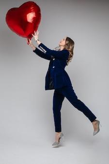 Toute la longueur de la jolie femme de race blanche en costume de velours bleu avec veste et pantalon et talons hauts étincelants tenant le symbole en forme de coeur rouge de ballon d'amour