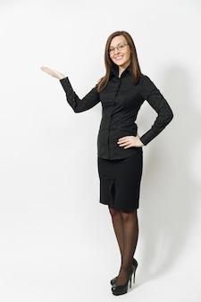 Toute la longueur d'une jolie jeune femme d'affaires souriante aux cheveux bruns en chemise classique noire, jupe, lunettes pointant la main de côté isolée sur mur blanc