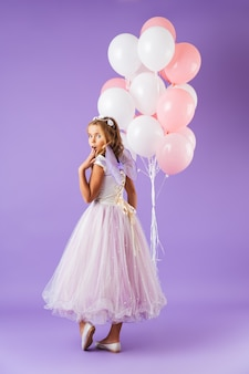 Sur toute la longueur d'une jolie petite fille habillée en robe de princesse debout isolé sur mur violet, tenant un bouquet de ballons