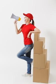 Toute la longueur de la livraison amusante femme au bonnet rouge, t-shirt isolé sur fond blanc. courrier féminin criant dans les nouvelles chaudes du mégaphone, debout près de boîtes en carton vides. réception du colis. espace de copie.