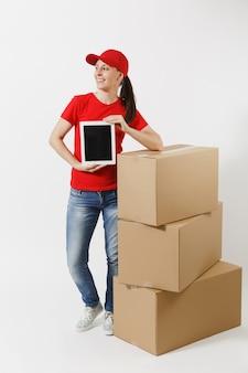 Toute la longueur de la livraison jeune femme au bonnet rouge, t-shirt isolé sur fond blanc. courrier féminin près de boîtes en carton, ordinateur tablette, écran vide noir vierge. réception du colis. espace de copie.