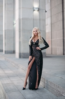 Toute la longueur de la magnifique femme blonde mince avec de longs cheveux ondulés et de gros seins posant dans une robe noire étincelante et des talons hauts dans la rue.
