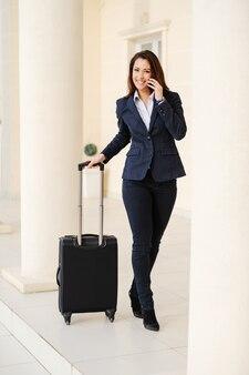 Toute la longueur de la séduisante brunette souriante caucasienne habillée décontractée intelligente tirant des bagages et utilisant un téléphone intelligent pour appeler un taxi concept de voyage d'affaires.
