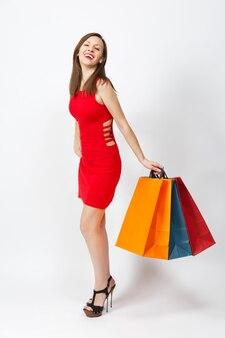 Toute la longueur de la séduisante jeune femme caucasienne glamour aux cheveux bruns en robe rouge tenant des paquets multicolores avec des achats après le shopping isolé sur fond blanc. copiez l'espace pour la publicité.
