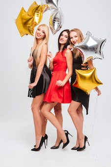 Toute la longueur de trois jeunes femmes séduisantes souriantes avec des ballons en forme d'étoile sur fond blanc