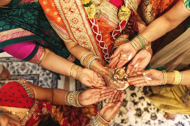 Toutes les femmes de la famille indienne tiennent des épices sur leurs paumes