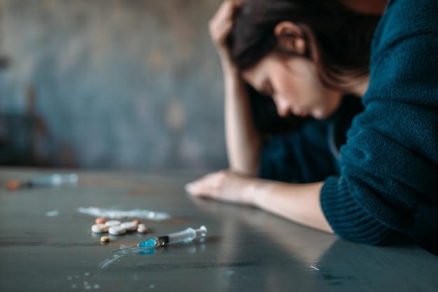 Toxicomane assis à la table avec des stupéfiants
