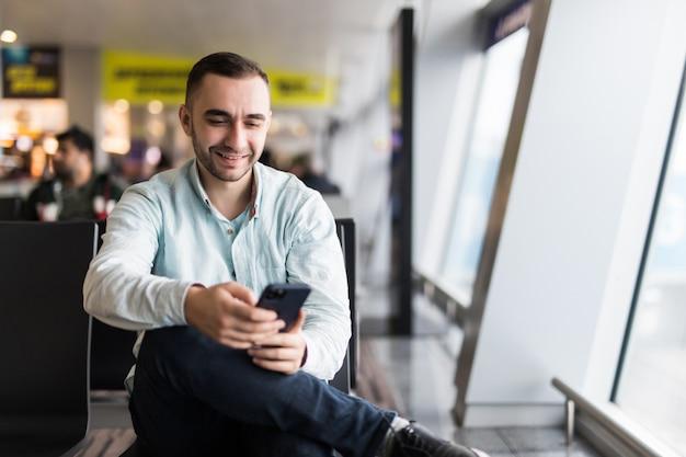 Tportrait de bel homme en tenue décontractée tenant ses bagages et la messagerie via son téléphone portable assis dans le hall de l'aéroport