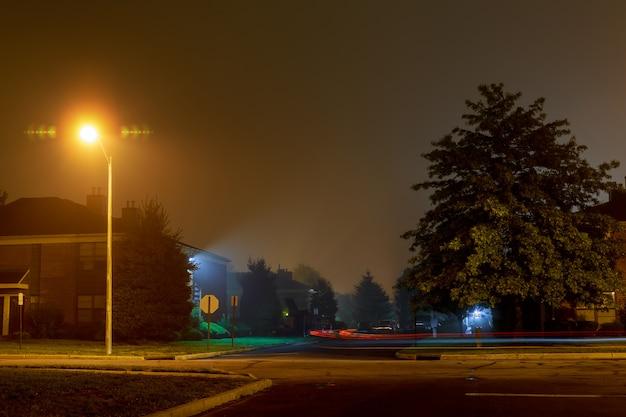 Trace de voiture sur une route de nuit vide dans un brouillard