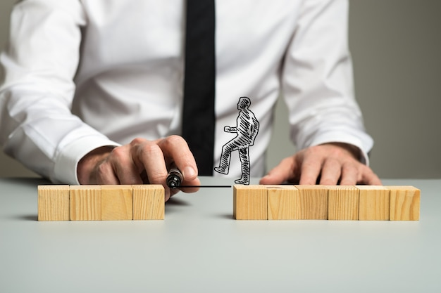 Tracer une ligne entre deux piles séparées de blocs de bois pour un homme d'affaires en silhouette